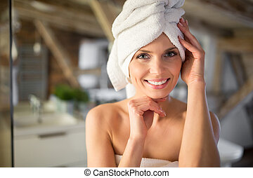 Beautiful woman wrapped in towels smiling