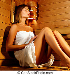 Beautiful woman wrapped in white towel takes a wooden sauna.