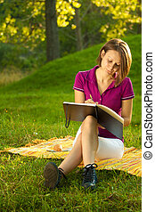 Beautiful woman writing in her diary in the park