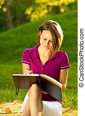 Beautiful woman writing in her diary