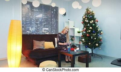 Beautiful woman writing letter on Christmas sitting on sofa near the xmas tree