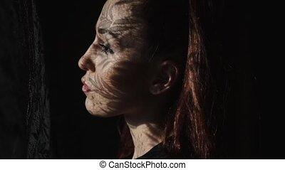 Beautiful woman's portrait with lace pattern shadow and sun...