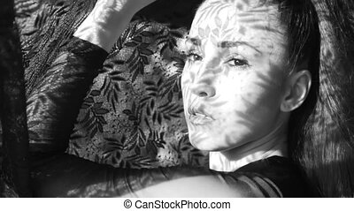 Beautiful woman's portrait with lace pattern shadow and  sun light on her face