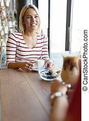 Beautiful women drinking coffee and gossiping