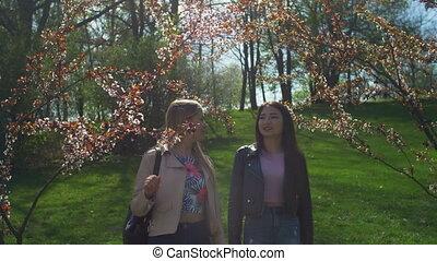 Beautiful women enjoying smell in spring park