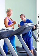 Beautiful women exercising in gym with personal fitness trainer