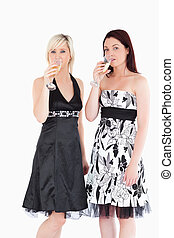 Beautiful women in dresses drinking champagne