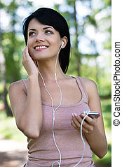 Beautiful women in park. Beautiful young women in headphones listening to the music while walking in park