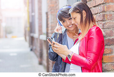 beautiful women is sharing information with smartphone in the city