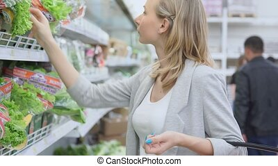 Beautiful women shopping vegetables and fruits in supermarket, fresh salad.