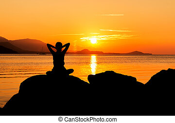 beautiful women sitting on the beach sunset background