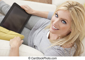 Beautiful Women Using Tablet Computer At Home on Sofa -...