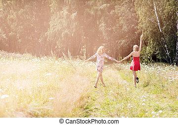 Beautiful women walking in the summer park.