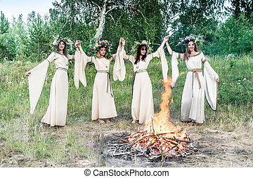 Attractive Women with Wreath of Flowers dancing around bonfire. Ivan Kupala Holiday Celebration. Russia