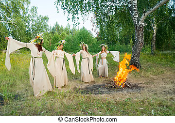 Beautiful women with flower wreath near bonfire