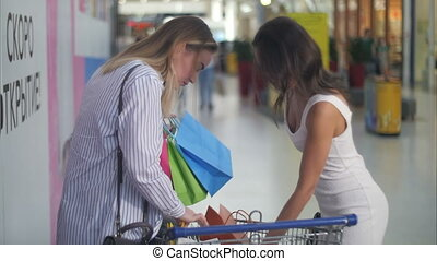 Beautiful women with shopping cart near supermarket serching for something