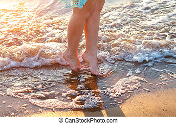 beautiful women's bare feet by the sea on the waves relaxation concept