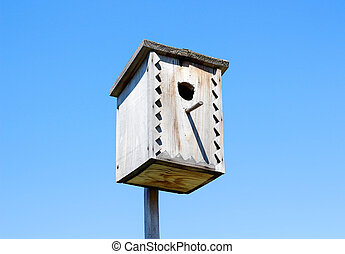 Beautiful wooden birdhouse. On the background of blue sky in a Sunny day.