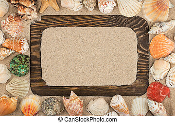 Beautiful wooden frame, stars and seashells on the sand background, with place for your image, text.