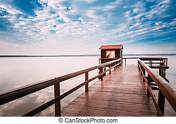 Beautiful wooden pier for fishing, small wooden house shed and beautiful lake or river in background.