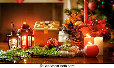 Beautiful wooden table decorated for Christmas celebrations against burning fireplace