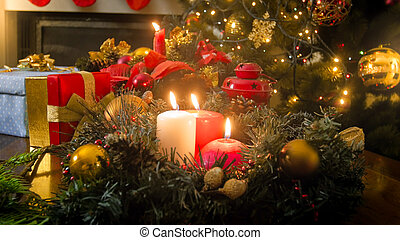Beautiful wooden table decorated with burning candles, wreath and lanterns for celebrating Christmas