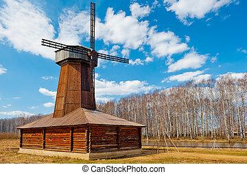 Beautiful wooden windmill in a field in spring