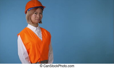 portrait young asian female posing wearing orange hard hat vest showing hand gesture thumbs up on blue background in studio. attractive korean woman with blond hair wearing white casual shirt looking at the camera smiling
