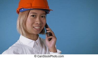 beautiful worker in uniform talking by mobile