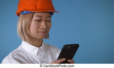 beautiful worker in uniform texting on mobile