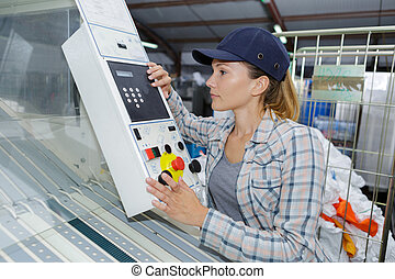 beautiful worker operating a machine in a factory