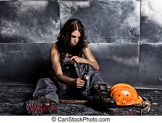 Beautiful worker with a pickaxe and helmet. Seductive and beautiful woman miner sitting on a floor on steel background