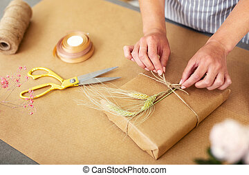 Nice female decorator packing a gift