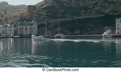 Beautiful yacht goes through harbour of the Black sea on the background of town, houses, yachts and picturesque landscapes