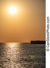 Beautiful yellow and orange sunset over the sea. The sun goes down over the sea. Silhouette of a pier at sunset