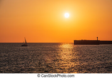 Beautiful yellow and orange sunset over the sea. The sun goes down over the sea. Silhouette of sea port at sunset