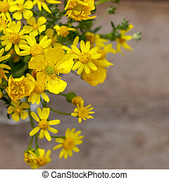 beautiful yellow bouquet of flowers stands on a wooden background, copy space