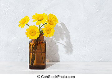 beautiful Yellow flowers in amber bottle on wooden table. Spring scene background. Copy space