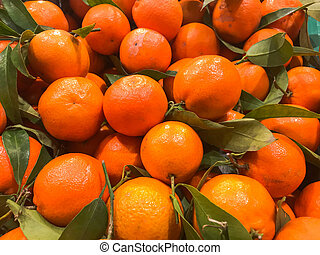 Beautiful yellow, orange, natural, sweet, tasty, ripe, soft, round, bright tangerines, fruits, clementines with green leaves. Texture, background
