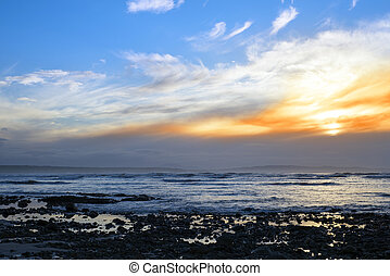 beautiful yellow sunset sky over rocky beach