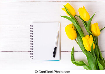 Beautiful yellow tulips, empty paper notebook on white wooden background.