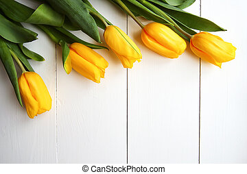Beautiful yellow tulips on wooden background, copyspace
