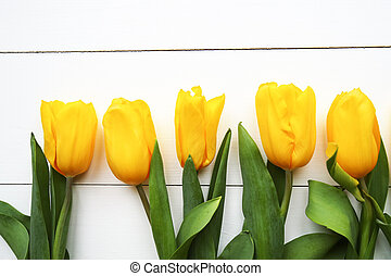 Beautiful yellow tulips on wooden white background, space for text