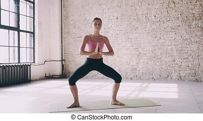 Beautiful yoga girl doing asanas in studio
