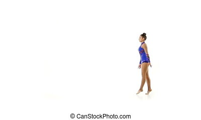 Beautiful young acrobat performs gymnastic stunt on a white background slow motion