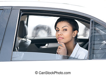 Beautiful young african american woman sitting in car and looking at camera