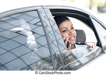 Beautiful young african american woman sitting in car and talking on smartphone
