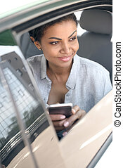 Beautiful young african american woman sitting in car and using smartphone