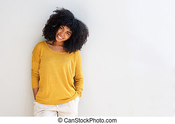 Beautiful young african american woman standing against white background with hands in pocket