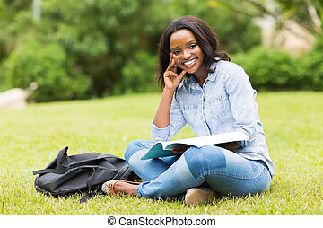 young african college girl sitting on grass